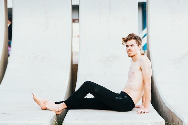 Portrait de jeune homme aux cheveux roux avec des taches de rousseur, exercice torse nu.