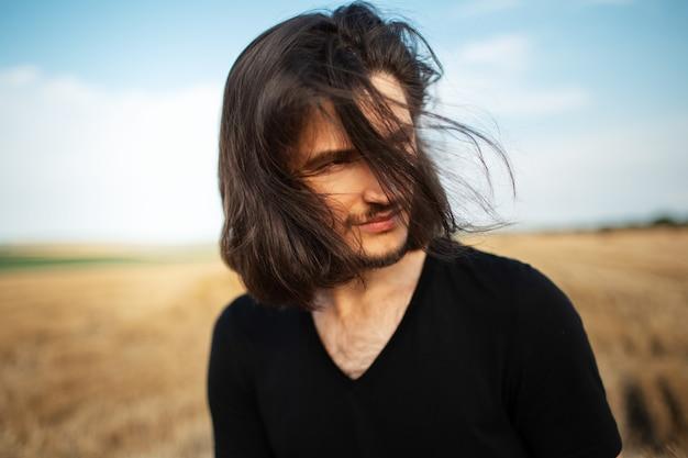 Portrait de jeune homme aux longs cheveux bruns dans le champ de blé.