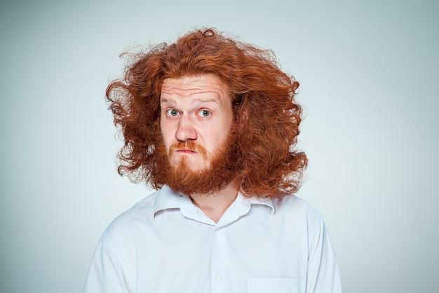 Portrait de jeune homme aux longs cheveux roux et avec une expression faciale choquée sur fond gris