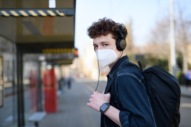 Un portrait d'un jeune homme de banlieue debout sur un arrêt de bus à l'extérieur de la ville, concept de coronavirus.