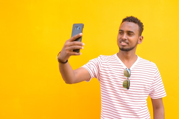 Portrait de jeune homme barbu africain beau avec des cheveux afro contre le mur jaune dans les rues à l'extérieur