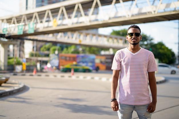 Portrait de jeune homme barbu africain beau avec des cheveux afro contre vue sur la passerelle dans les rues de la ville à l'extérieur