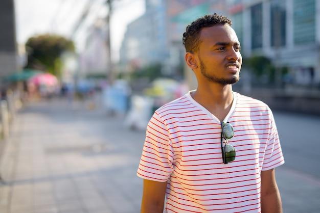Portrait de jeune homme barbu africain beau avec des cheveux afro dans les rues de la ville à l'extérieur