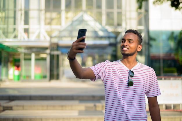 Portrait de jeune homme barbu africain beau avec des cheveux afro explorer les rues de la ville à l'extérieur