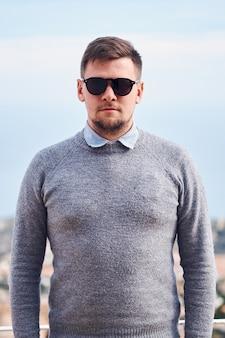 Portrait d'un jeune homme barbu attrayant à lunettes de soleil noir