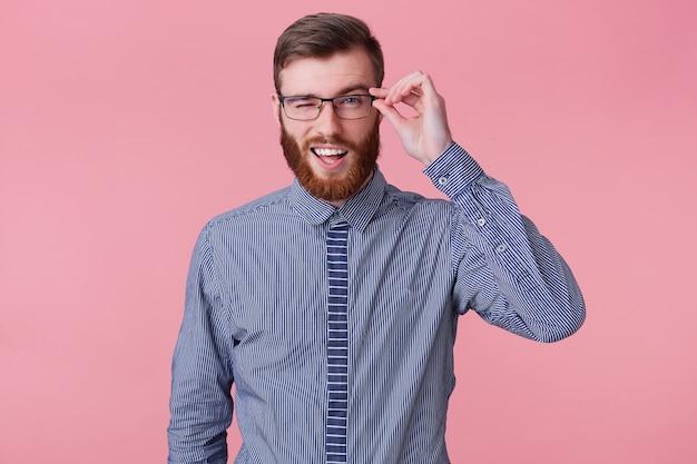Portrait de jeune homme barbu attrayant souriant dans une chemise rayée, détient des lunettes et des clins d'œil isolés sur fond rose.