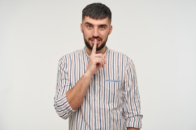 Portrait de jeune homme barbu aux yeux bruns aux cheveux courts en gardant l'index sur ses lèvres tout en regardant et en soulevant un sourcil, isolé sur un mur blanc