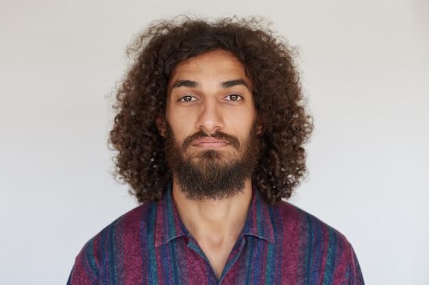 Portrait de jeune homme barbu aux yeux bruns avec des cheveux bouclés foncés à la recherche avec un visage calme, gardant les lèvres pliées