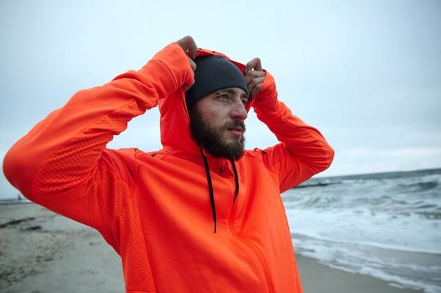 Portrait de jeune homme barbu brune attrayante dans des vêtements sportifs chauds mettant le capot en se tenant debout sur le littoral de la mer après la séance de course du matin