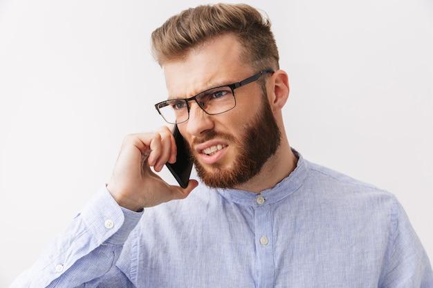 Portrait d'un jeune homme barbu en colère à lunettes