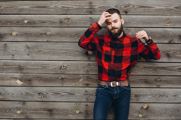 Portrait d'un jeune homme barbu élégant, habillé en jeans et un vrai travailleur noir en chemise rouge.