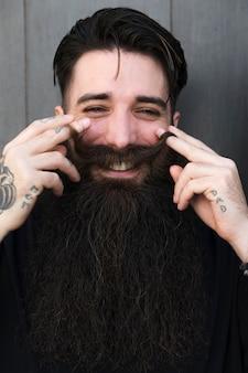 Portrait de jeune homme barbu élégant tourbillonnant moustache et regardant la caméra