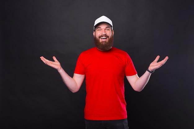 Portrait de jeune homme barbu heureux en t-shirt rouge faisant un geste de bienvenue