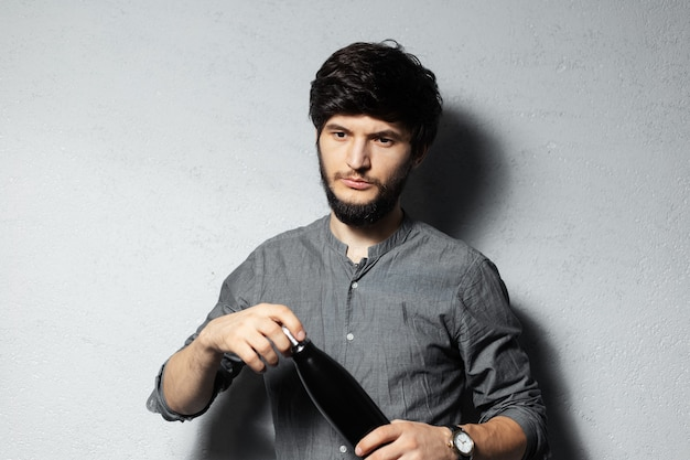 Portrait de jeune homme barbu, ouvre une bouteille en acier thermo noir pour l'eau