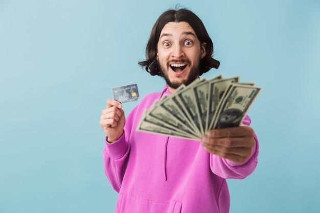 Portrait d'un jeune homme barbu portant des vêtements décontractés, isolé sur un mur, montrant des billets en argent et une carte de crédit
