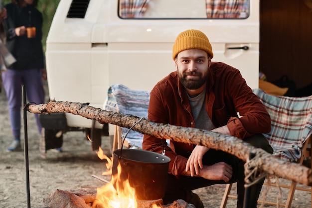 Portrait de jeune homme barbu regardant la caméra pendant la cuisson des aliments sur un feu pendant le camping dans la forêt