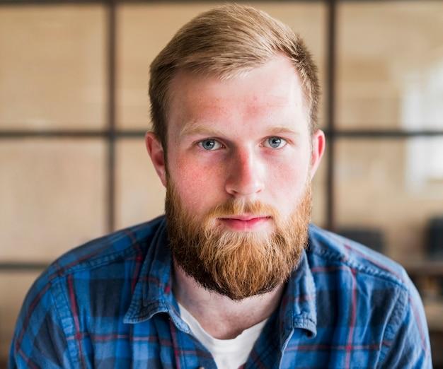 Portrait de jeune homme barbu, regardant la caméra