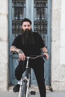 Portrait d'un jeune homme barbu avec son vélo