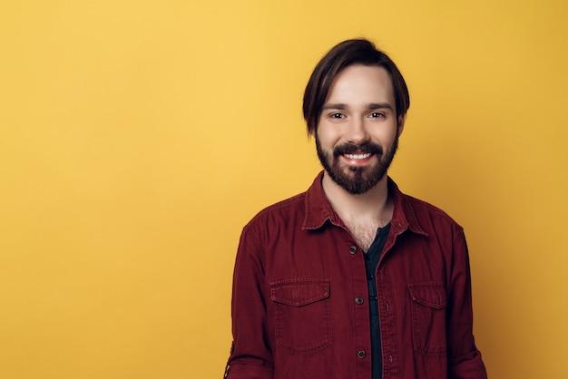 Portrait de jeune homme barbu souriant.