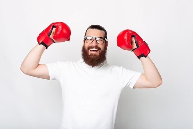Portrait de jeune homme barbu en t-shirt blanc célébrant la victoire et portant des gants de boxe rouges
