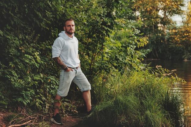 Portrait de jeune homme barbu avec des tatouages en veste blanche à la campagne ou dans le parc. un homme en tenue décontractée passe la soirée dans la nature. concept de style, marche au grand air et unité avec la nature