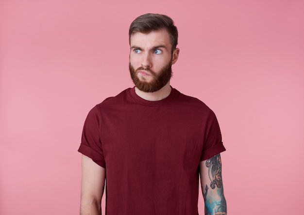 Portrait de jeune homme barbu tatoué beau malentendu rouge en t-shirt rouge, se dresse sur fond rose, pensant à quelque chose, regarde ailleurs.