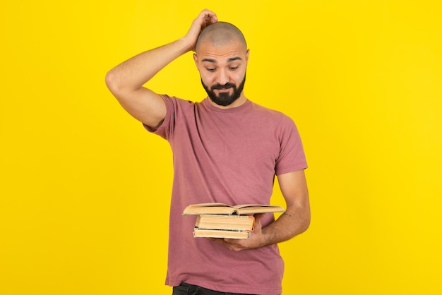 Portrait d'un jeune homme barbu tenant des livres sur un mur jaune.