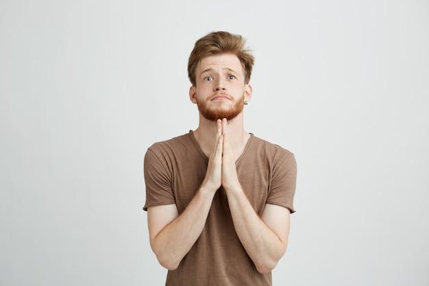 Portrait de jeune homme beau avec barbe priant en espérant.