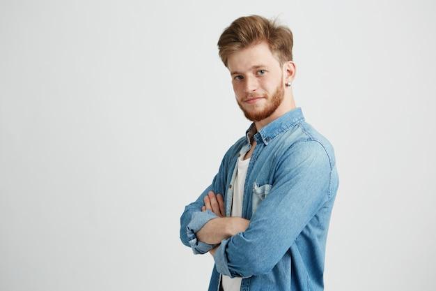 Portrait de jeune homme beau confiant souriant avec les bras croisés.