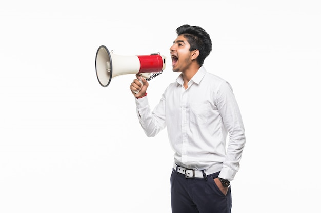 Portrait de jeune homme beau crier à l'aide d'un mégaphone isolé sur mur blanc