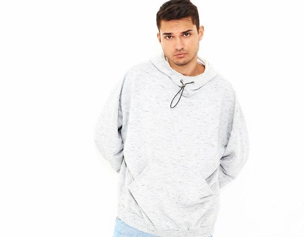 Portrait de jeune homme beau modèle habillé en vêtements à capuche gris décontracté posant sur le mur blanc. isolé