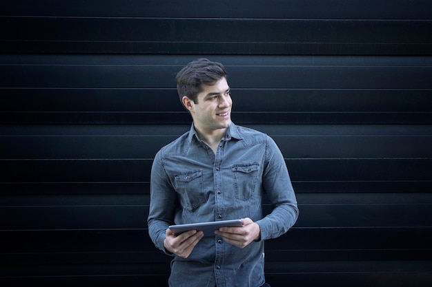 Portrait de jeune homme beau souriant tenant la tablette et regardant de côté