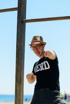 Portrait de jeune homme beau touriste comme nerd à la plage en espagne