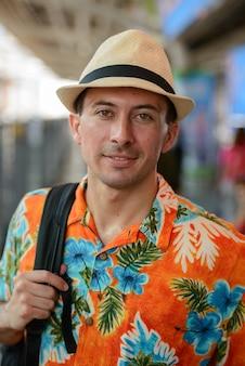 Portrait de jeune homme beau touriste à la gare du ciel dans la ville