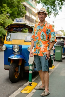 Portrait de jeune homme beau touriste avec tuk tuk comme transport public local dans la ville de bangkok