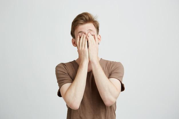 Portrait de jeune homme blond fermant le visage avec les mains.