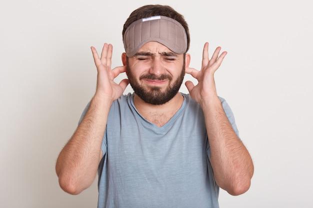 Portrait de jeune homme bouchant les oreilles avec les index et gardant les yeux fermés