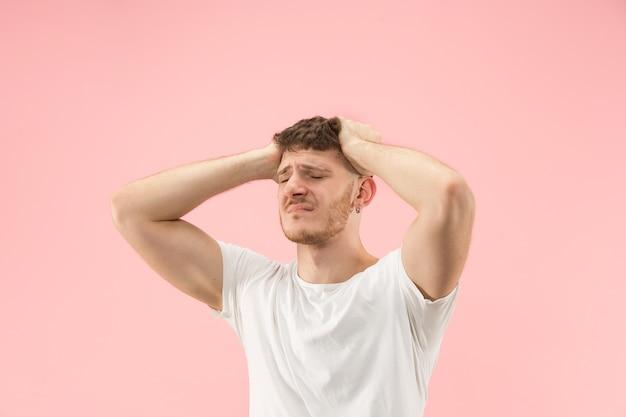 Portrait de jeune homme branché sur fond rose. expression émotionnelle.