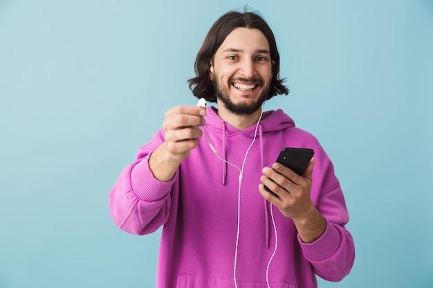 Portrait d'un jeune homme brun barbu heureux portant un sweat à capuche debout isolé sur un mur bleu, écoutant de la musique avec des écouteurs, tenant un téléphone portable