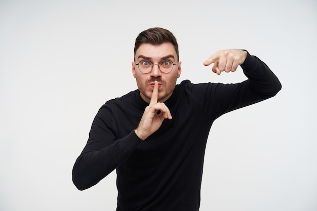 Portrait de jeune homme brune aux cheveux courts en colère pointant croisé avec l'index tout en montrant le geste de silence, isolé sur blanc