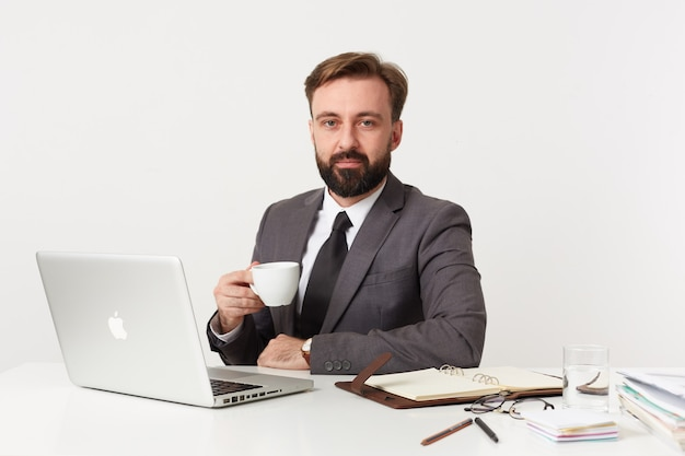 Portrait de jeune homme brune barbu avec coupe de cheveux courte à l'avant avec un visage calme tout en travaillant avec son ordinateur portable et ordinateur portable sur un mur blanc, ayant une tasse de thé