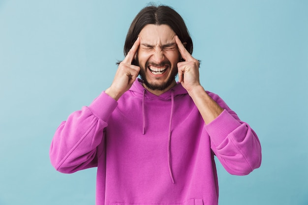 Portrait d'un jeune homme brune barbu stressé portant un sweat à capuche debout isolé sur un mur bleu, souffrant d'un mal de tête