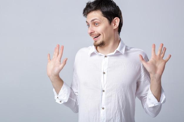 Portrait de jeune homme brune souriant séduisant en chemise blanche sur fond gris.