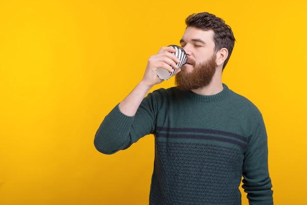 Portrait de jeune homme buvant du café sur le mur jaune