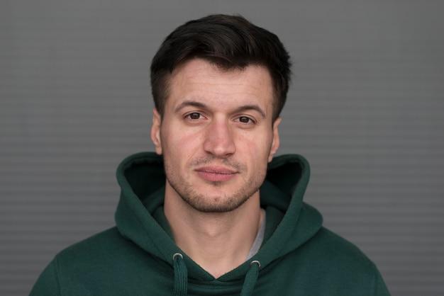 Portrait jeune homme avec capuche vert