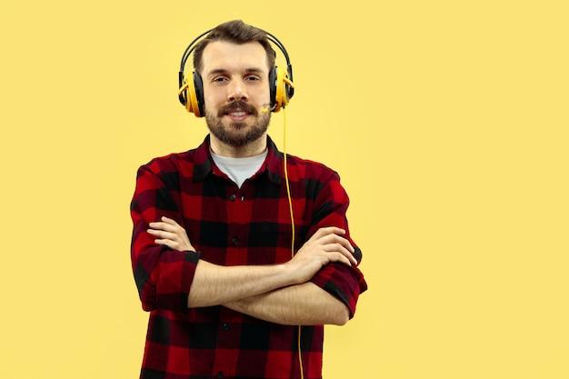 Portrait de jeune homme avec un casque sur mur jaune