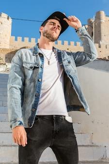 Portrait d'un jeune homme avec une casquette et une veste en jean