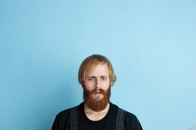 Portrait de jeune homme caucasien a l'air rêveur, mignon et heureux. recherche et réflexion sur l'espace bleu