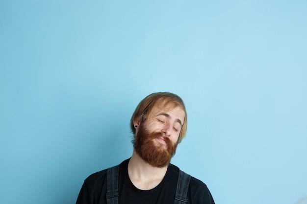 Portrait de jeune homme caucasien a l'air rêveur, mignon et heureux. recherche et réflexion sur fond de studio bleu. copyspace pour votre publicité. concept d'avenir, cible, rêves, visualisation.