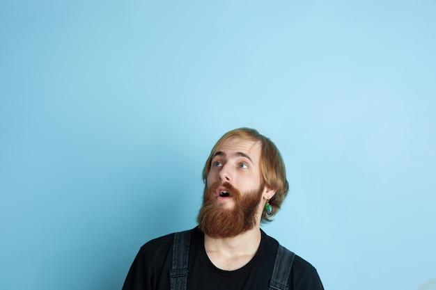 Portrait de jeune homme caucasien a l'air rêveur, mignon et heureux